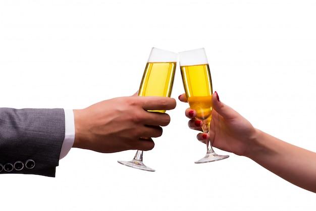 白で隔離されるシャンパンのグラスと手