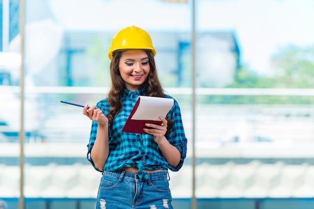 Женщина строитель заметок на строительной площадке