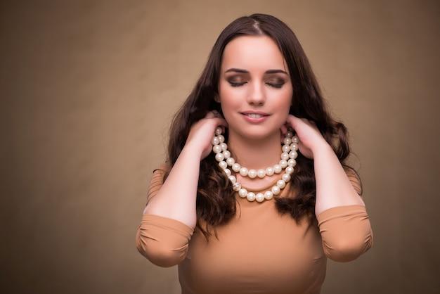 真珠のネックレスを持つ若い女