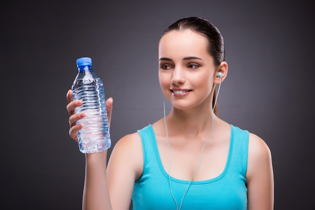 Женщина занимается спортом с бутылкой пресной воды
