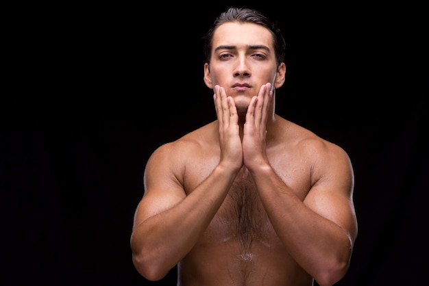 暗い背景にシャワーを浴びた後男