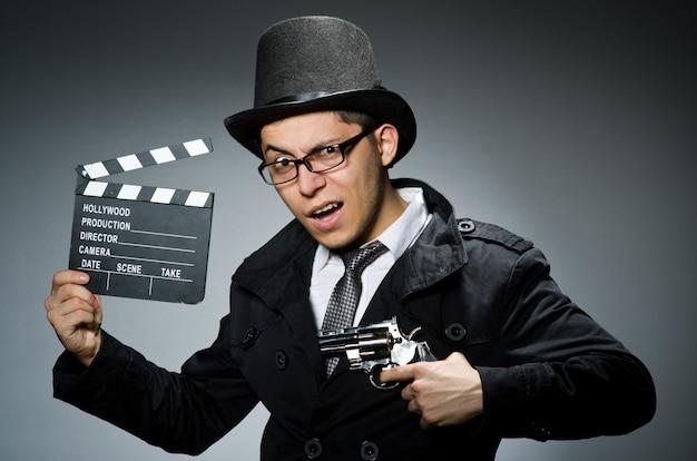 Молодой человек с оружием и вагонкой против серого