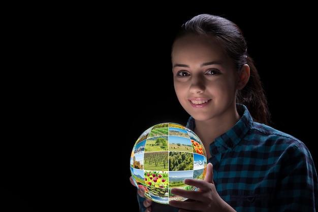 Молодая женщина держит землю с фотографиями природы