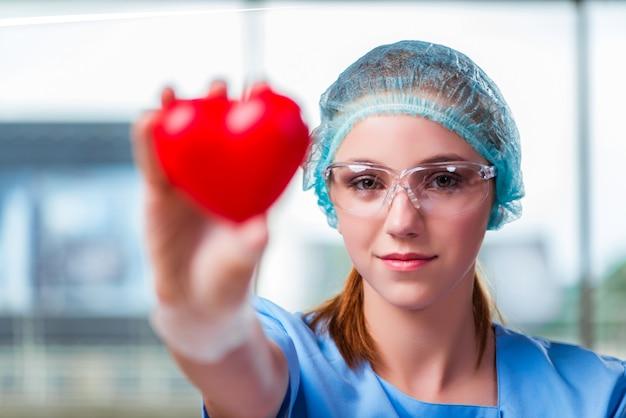 Доктор держит красное сердце в медицинской концепции