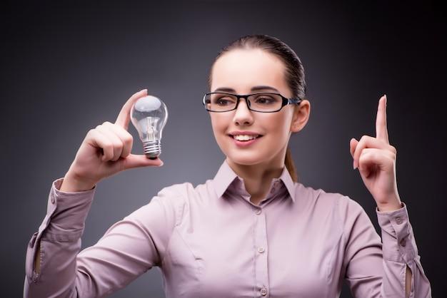 Молодая коммерсантка в концепции идеи с электрической лампочкой