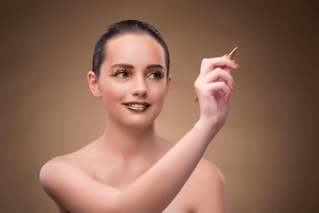 ファッション概念の黄金のペンを持つ女性