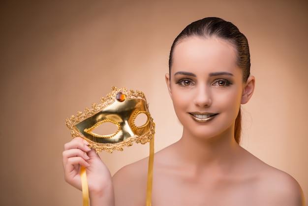 カーニバルの概念でマスクを持つ若い女