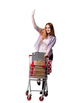 ショッピングカートと白で隔離されるバッグを持つ女性