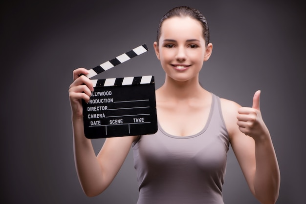映画館のコンセプトで映画板を持つ女性
