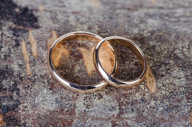 Два золотых обручальных кольца на деревянном фоне
