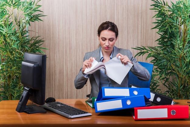 Женщина бросает документы в офисе в состоянии стресса
