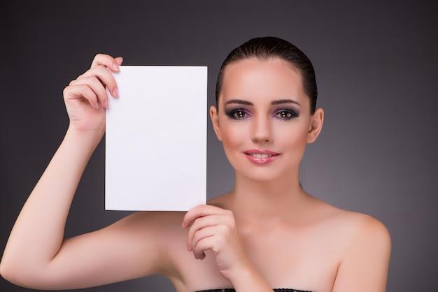 空白のメッセージ紙を持つ美しい女性