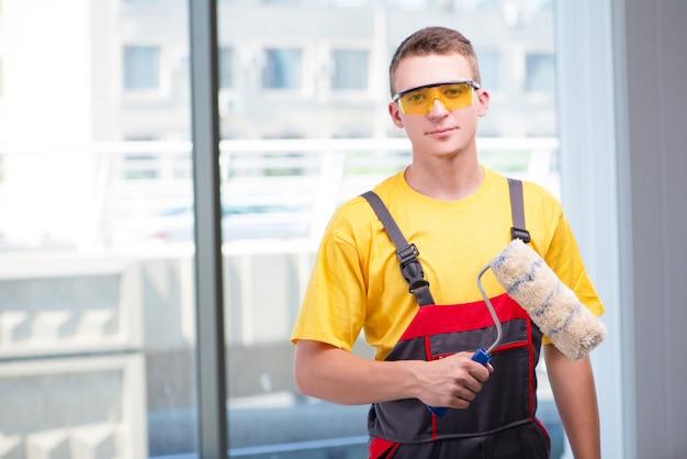 Молодой строитель в желтых комбинезонах