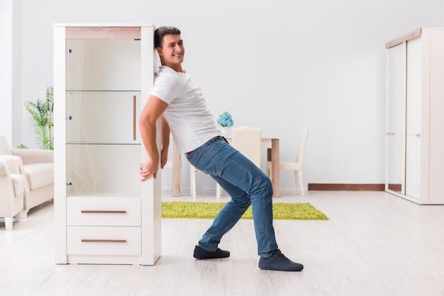 家で家具を移動する男