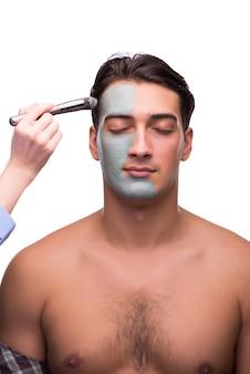 白に適用されているフェイスマスクを持つ男