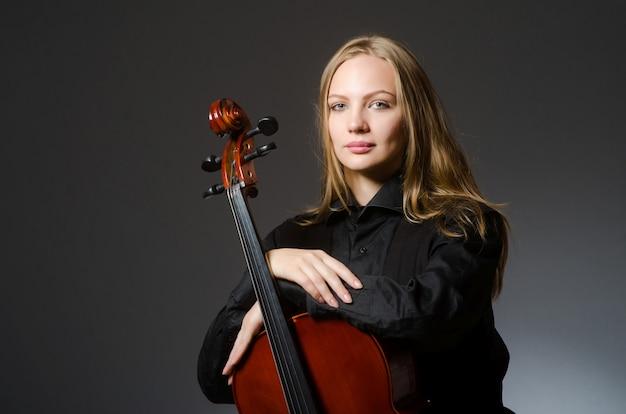 音楽のコンセプトで古典的なチェロを弾く女性