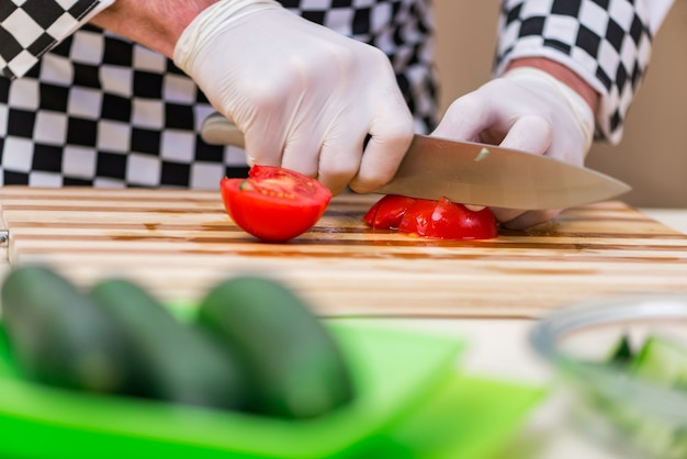男性の料理人が台所で食べ物を準備する