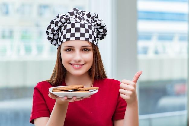 若い料理人が台所でクッキーを準備する