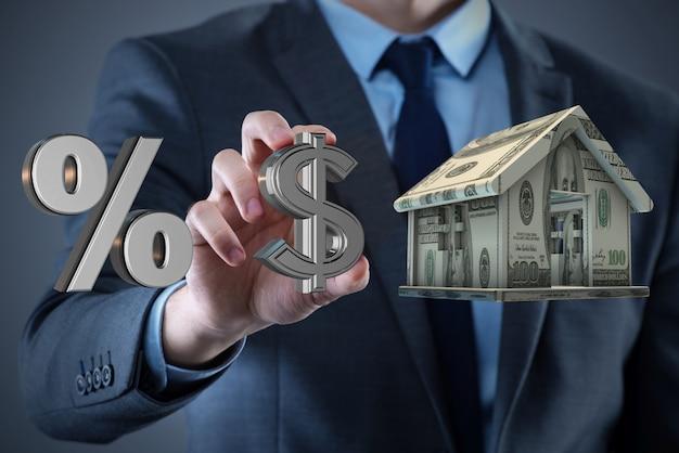 Молодой красивый бизнесмен держит дом