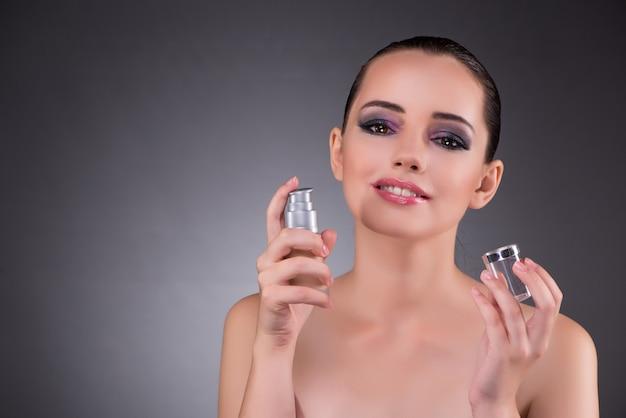 美しさの概念で香水を持つ若い女