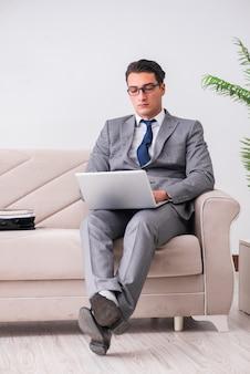 ソファに座ってラップトップノートを持ったビジネスマン