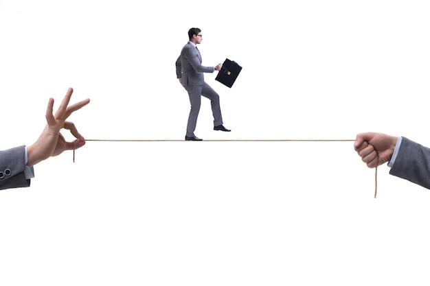 ビジネスコンセプトでタイトなロープの上を歩くビジネスマン