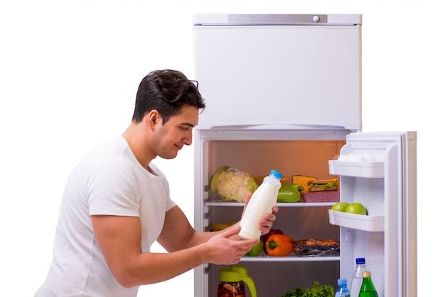 食品がいっぱい入った冷蔵庫の横にある男