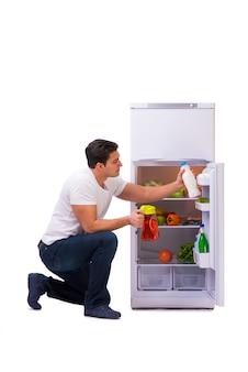 Человек рядом с холодильником, полным еды