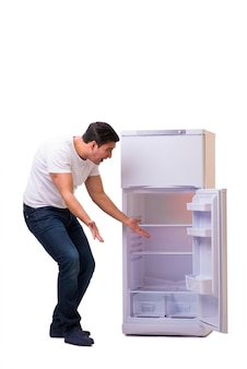 Мужчина ищет еду в пустом холодильнике