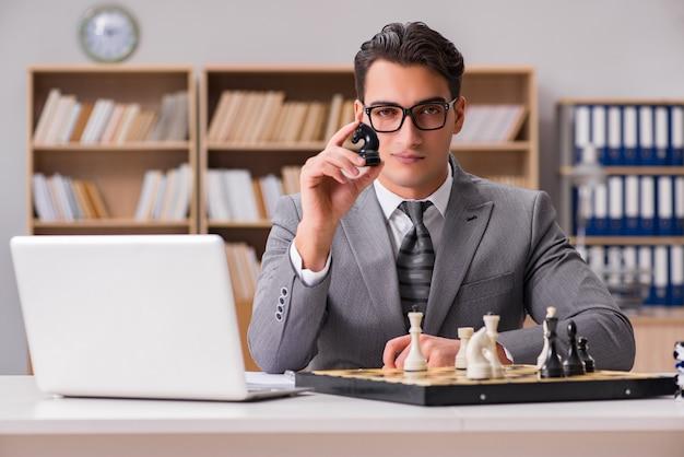オフィスでチェスをしている青年実業家