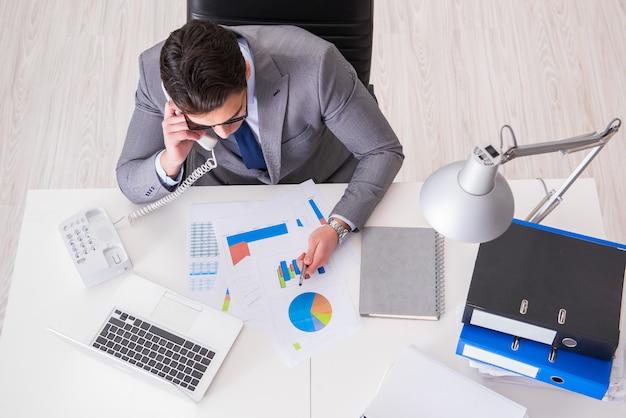 Взгляд сверху на бизнесмена работая на диаграммах дела