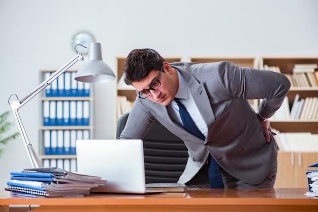 Бизнесмен чувствует боль в офисе
