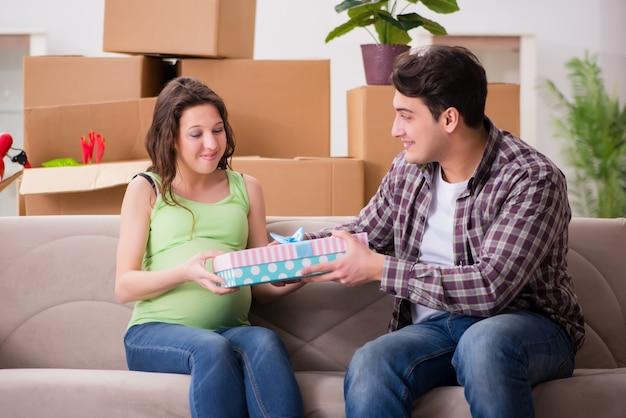 Молодая пара мужского и беременной жены с подарочной коробкой