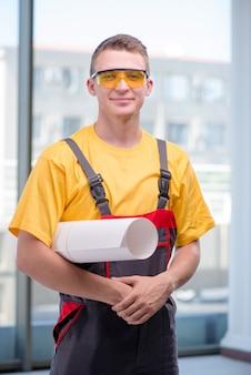 黄色のつなぎ服の若い建設労働者