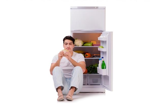 食べ物がいっぱい冷蔵庫の横にある男