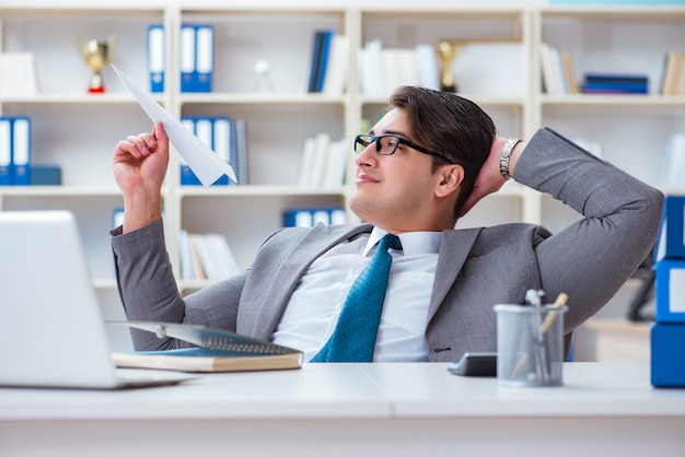 オフィスで紙飛行機を持ったビジネスマン