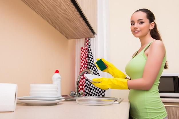 キッチンでお皿を洗う若い妻女性