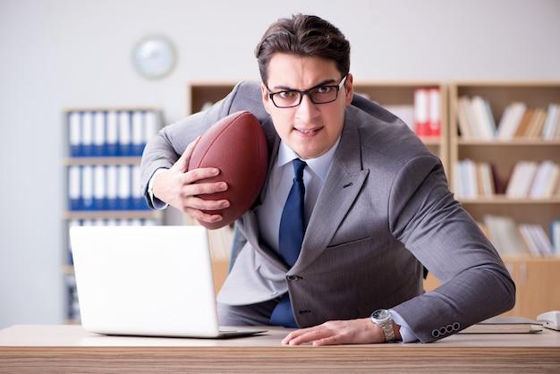 Бизнесмен с американским футболом в офисе