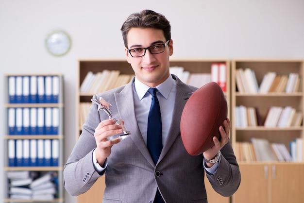 オフィスでアメリカンフットボールを持ったビジネスマン
