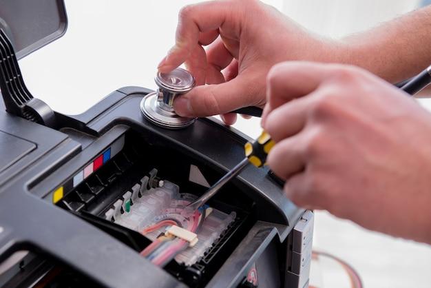 壊れたカラープリンターを修理する修理工