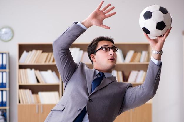 オフィスでサッカーボールを持ったビジネスマン