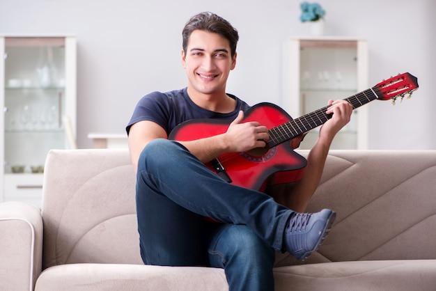 Молодой человек тренируется играть на гитаре у себя дома