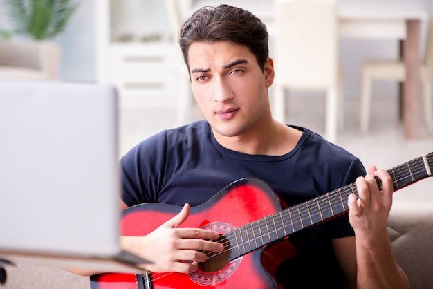 若い男が自宅でギターを弾く練習