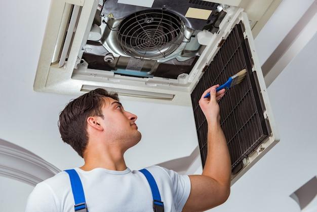 天井のエアコンユニットを修復する労働者