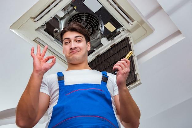 Работник ремонтирует потолочный кондиционер