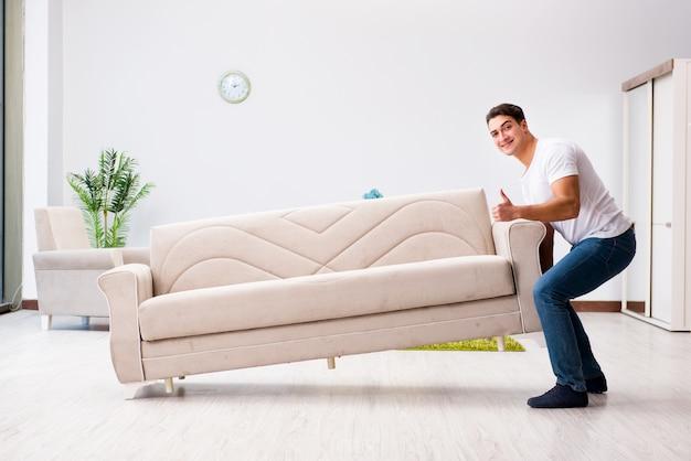 Молодой человек, перемещение мебели на дому