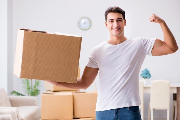 Молодой человек движется коробки дома