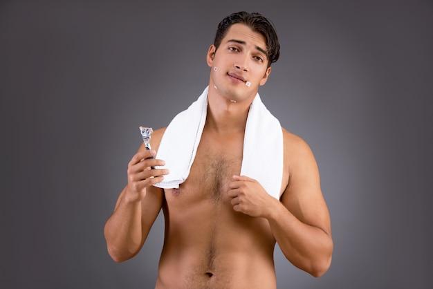 Красивый мужчина бритья против темноты