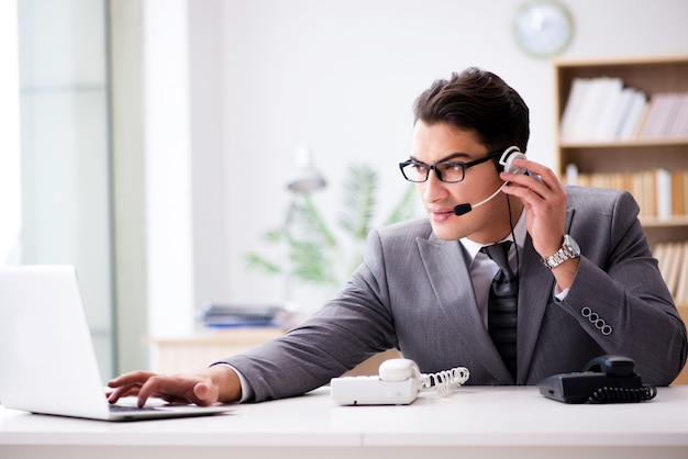 Оператор службы поддержки разговаривает по телефону в офисе