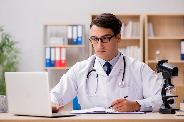 ラップトップコンピューターを持つ若い成人医師